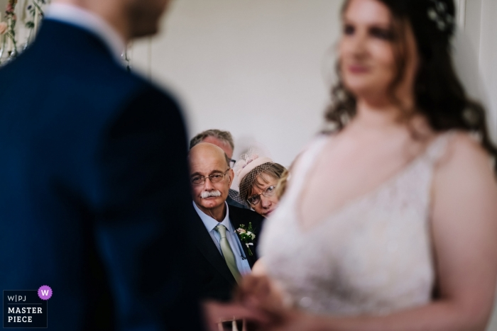 Hestercombe House Wedding Ceremony Photography - The Mother of the Bride struggles to get a good view of the ring exchange