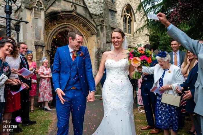 Kościół parafialny St. Mary's Ewell - Fotografia ślubna rzutu konfetti - Pan młody bierze ciężar konfetti - para idzie w naszym kierunku
