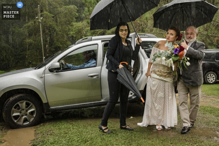 Trilhas do Araçari, Nova Friburgo, Rio de Janeiro - Bride getting out of car in the rain under umbrellas.