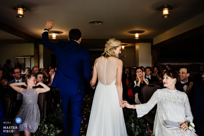 Chittenden, Vermont - Mountain Top Inn Wedding Photography | The bride, gives her mom's hand a squeeze as she recesses from the ceremony with her new husband.