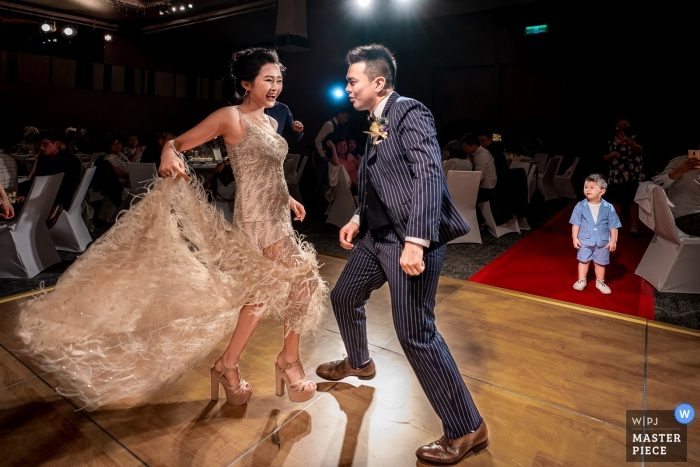 The couple were having their first dance as husband and wife. There was a little wedding guest attracted by their dance at Le Méridien in Taipei.