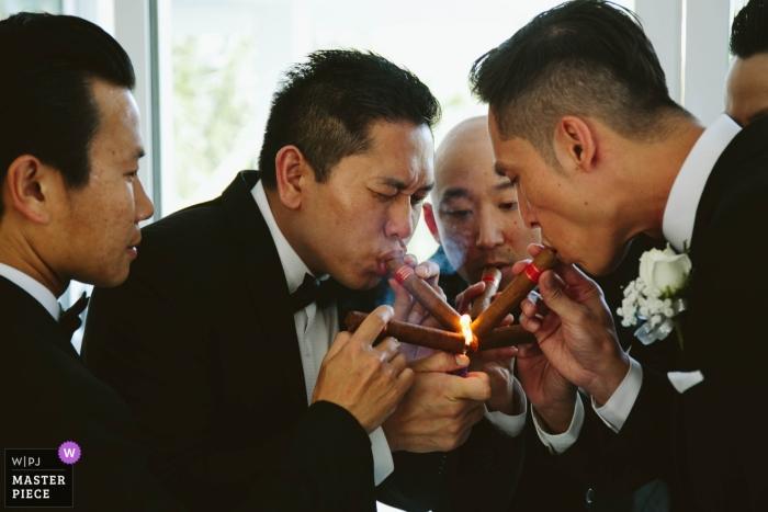 Hochzeitsfoto des Bräutigams und seiner Trauzeugen, die Zigarren im Victoria Resort in Hoi An anzünden.