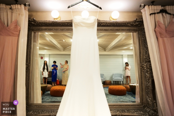 Bridal party and family reflected in mirror with the dress while waiting for ceremony at Oceanview Nahant.