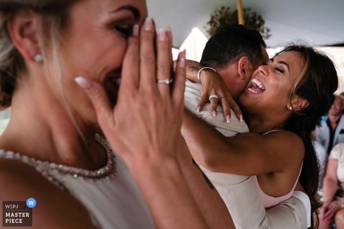 Pokojówka wiwatuje i przytula pana młodego, gdy panna młoda ociera łzy tuż po pocałunku w Golfclub Méan