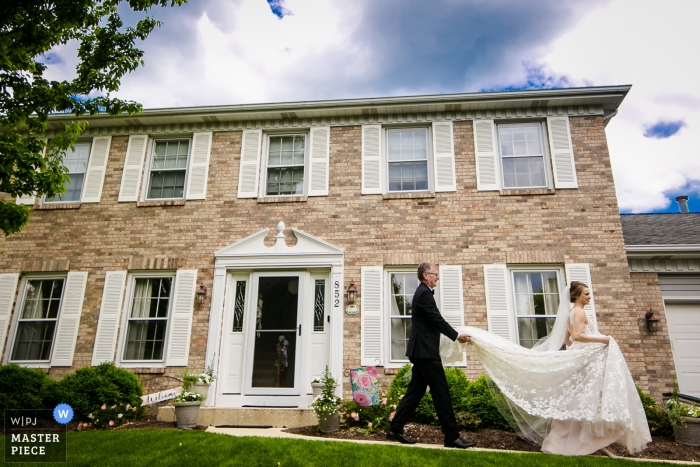 Holy Rosary Church wedding photography at Cantigny Park - the father helps with the bride's dress