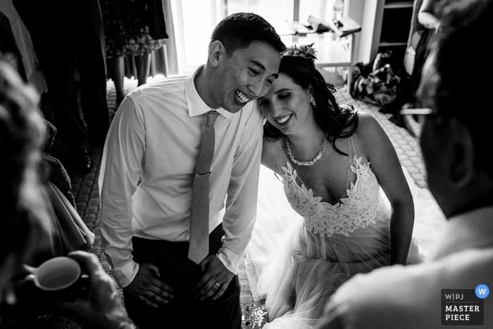 Trouwfotograaf voor het gastverblijf aan de haven in York Maine | De bruid en bruidegom lachen tijdens de traditionele theeceremonie op hun trouwdag