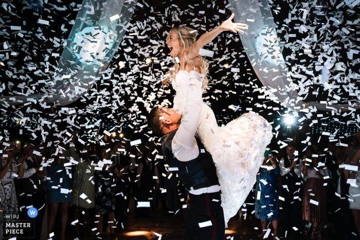Zdjęcie z przyjęcia weselnego w Rivington Barn przedstawiające pana młodego podnoszącego pannę młodą, gdy są oblewani konfetti.