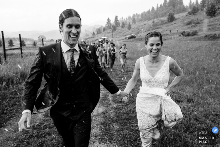 Rocky Creek Farm - Bozeman, Montana wedding photo of bride and groom running through the rain after the ceremony.
