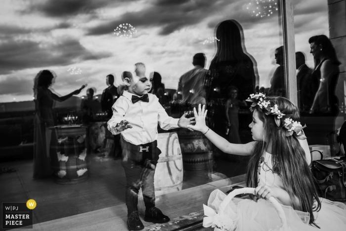 Katarzhina Estate, Svilengrad, Bulgaria wedding photo of children touching hands through glass at reception.