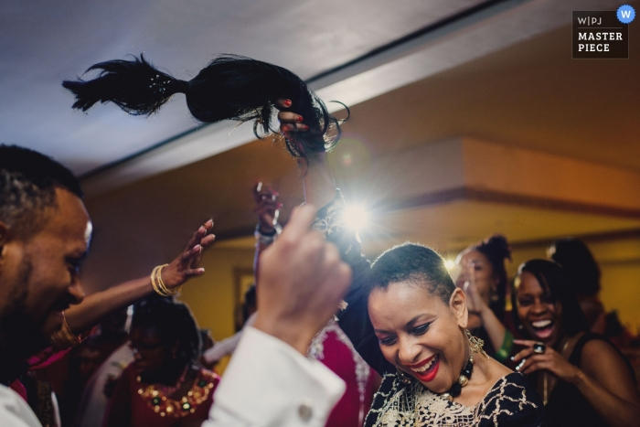 Wedding reception photo of a lady on the dance floor ripping off her wig and dancing like no-one is watching in London, England.