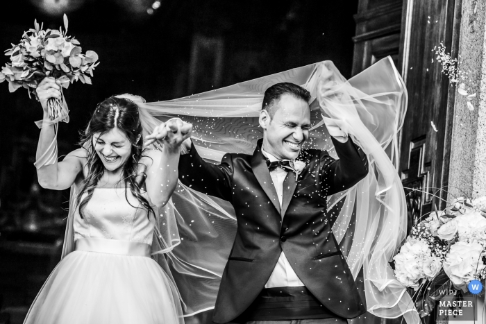 Black and white image of a bride and groom exiting Chiesa di San Giorgio as their guest shower them.