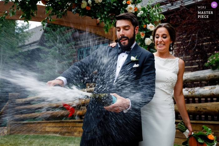 Wedding image of a bride with her groom taking the top of a bottle of champagne at their Ritz Carlton, Beaver Creek wedding.