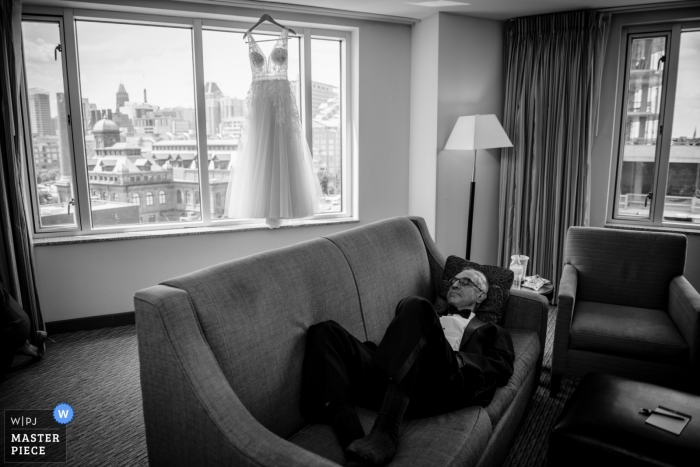 Baltimore, MD wedding photography of a father taking a nap while the girls get ready for the wedding.