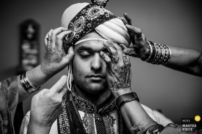Washington DC wedding photo of groom receiving help getting ready for his wedding..