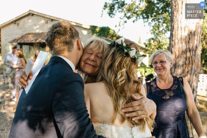 Mãe da noiva abraçando os noivos em seu casamento na Tenuta Corsignano, na Toscana.