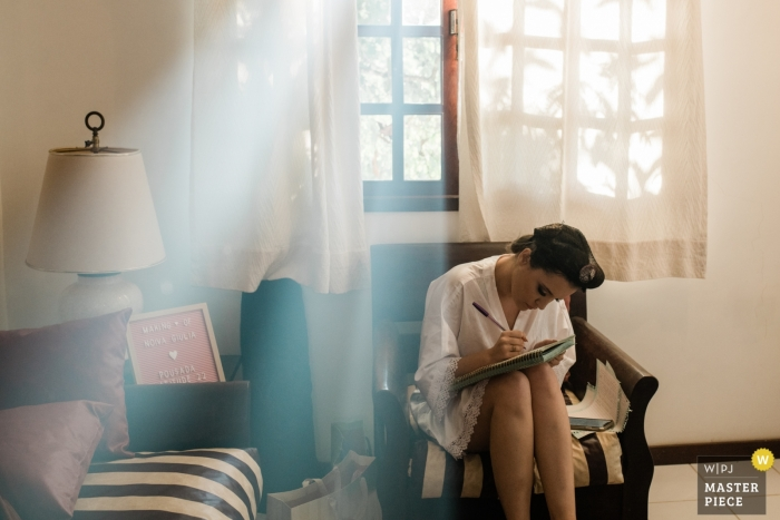 Photo of bride sitting and writing her vows before the Rio de Janeiro wedding ceremony.