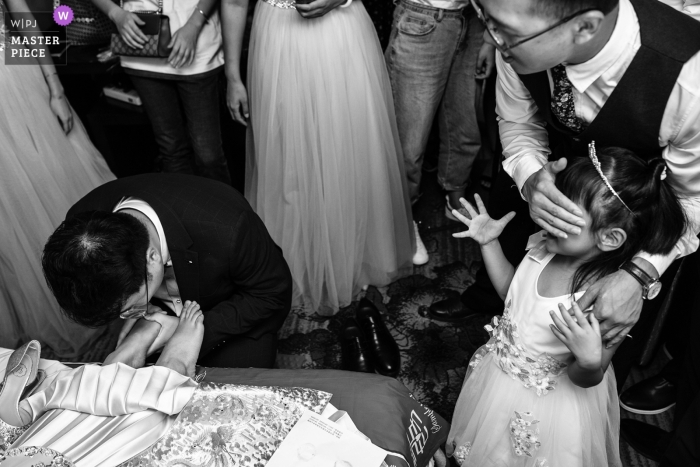This is the moment the dressed flower girl sees the bridegroom kissing the bride's foot. The moment he sees the bride kiss the bride's foot becomes a little shy. The best man goes to help the flower girl cover her eyes.