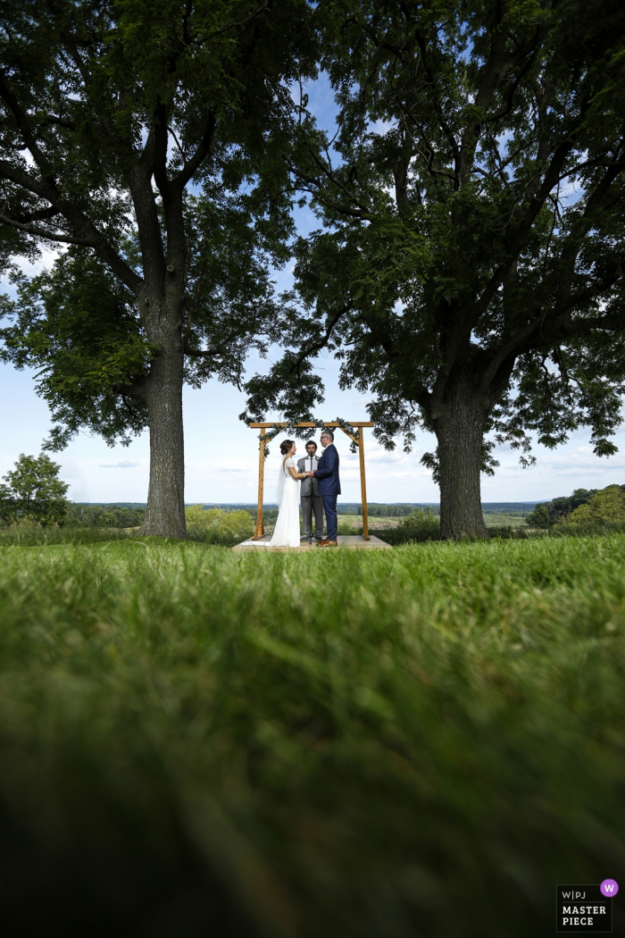 Photographer for weddings at Vennebu Hill, Wisconsin Dells, WI | The bride and groom join hands as they are married on a hill overlooking the Wisconsin River valley.