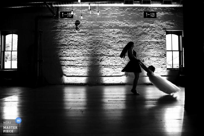 Le photojournaliste de mariage du Lagaret, Stoughton, WI. - Un invité fait pivoter la demoiselle autour de la piste de danse avant la première danse des jeunes mariés.