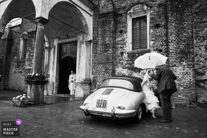 Fotografia ślubna z Tenuta Castello - klub golfowy Cerrione, Włochy panna młoda przybywająca do kościoła w deszczu