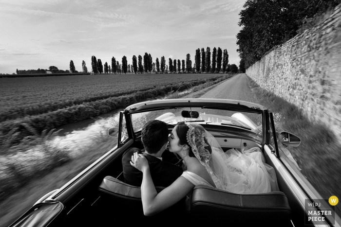Weddings at Strada dell' Annunciata, Medole, Mantova - Photographer riding with the bride and groom in the car En route to the restaurant after the ceremony.