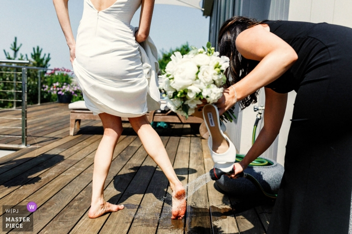 Wedding Photos from Wychmere Beach Club - Bridesmais helping the bride to wash her feet after going to the beach