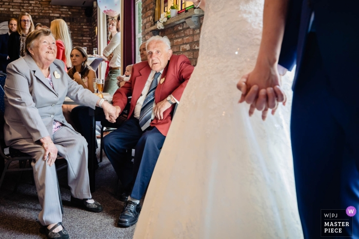 De Seterse Hoeve reception photography with bride, groom holding hands with elderly guests watching.