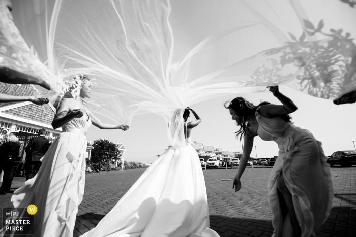 Czarno-białe zdjęcie panny młodej otrzymującej pomoc od druhen na ślub Wychmere Beach Club.
