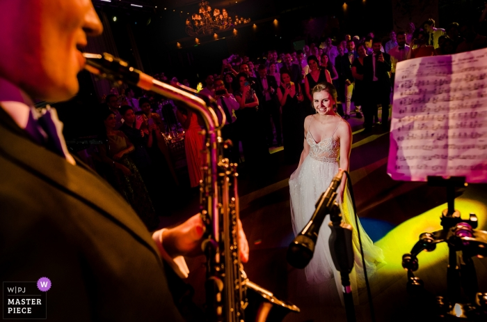 Bamboo Club, Bucharest Wedding venue photography   Bride watches as groom plays Lion King theme on the saxophone