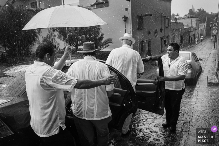 San Miguel de Allende, Mexico / The Rosewood hotel - Wedding photos of guests are loaded into taxis during a rain storm.