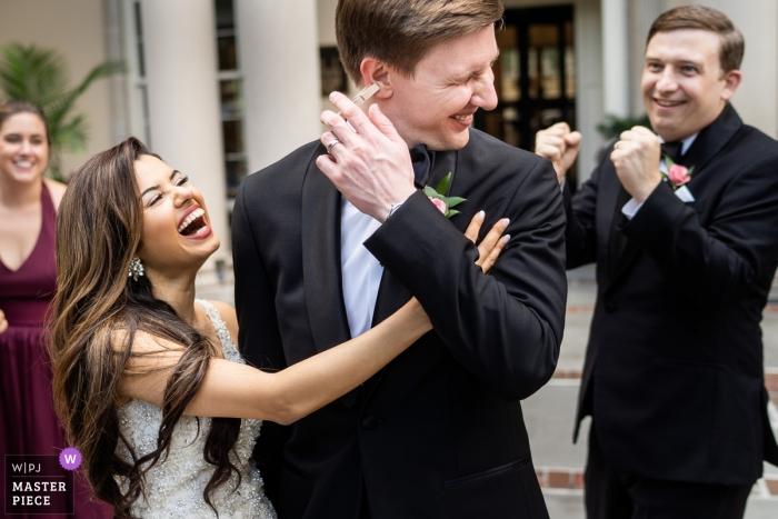 Biltmore Ballrooms Atlanta Wedding Venue Photography - Bride sneaks a clothespin on her grooms ear getting everyone a good laugh