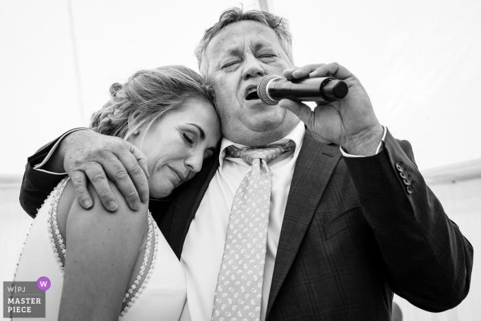 Father of the bride sings a song for his daughter while she seeks comfort in his arms at the Golf Club of Mean
