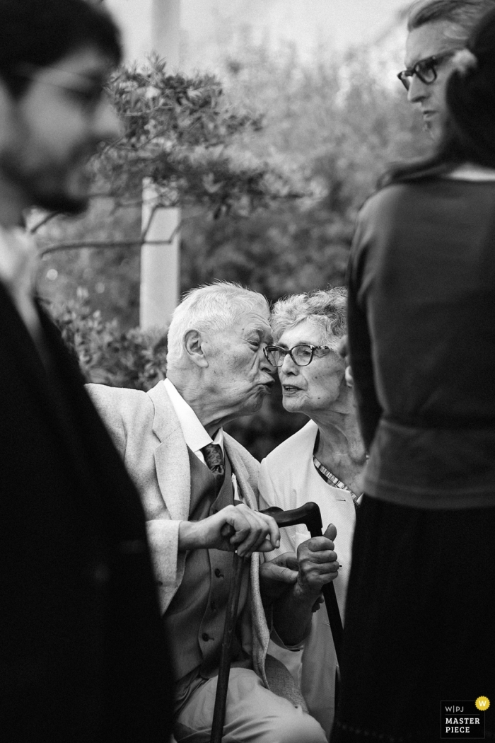 In front of the main hall in the town of Tierce - France Wedding Photographer | A kiss between the grandparents's of the groom