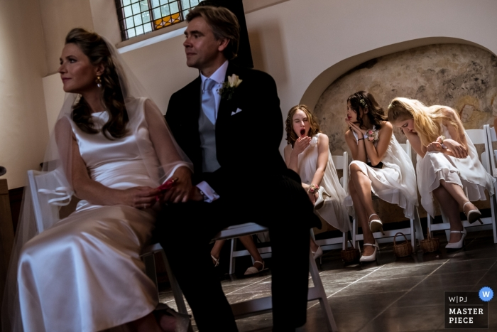Bridesmaids are bored during ceremony in Naarden - Wedding Reportage Photographer
