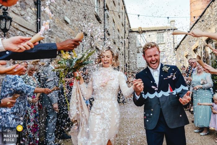 Fotos der Braut und des Bräutigams geduscht im Confetti mit dem Confetti, das ganz über das Brautgesicht bei Holmes Mill Cheshire UK geht