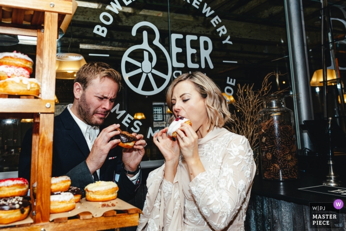 Holmes Mill Cheshire UK Wedding Photographers | Bride and groom eating cake an screwing up their faces