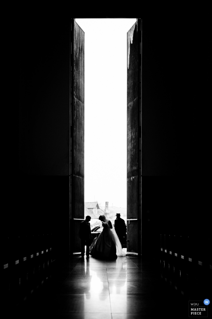 Black and white vertical image of the bride entering through the tall doors of the Vila Nova de Gaia for her wedding.