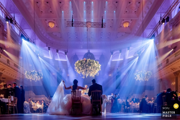 Musical hall in Amsterdam - Wedding Photos - The wedding couple dining in the centre of the venue as the rest of the guests are situated around round tables surrounding them.