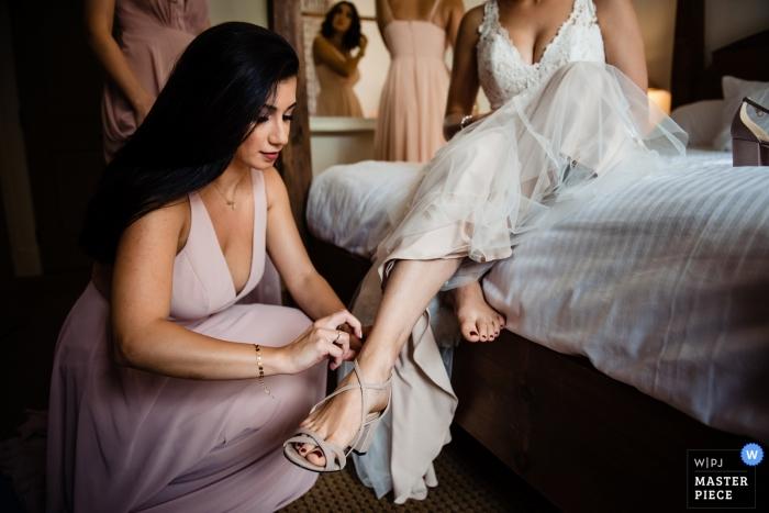 Sugarbush Resort in Warren, Vermont Hochzeitsfotograf - Eine Brautjungfer hilft der Braut mit ihren Schuhen.