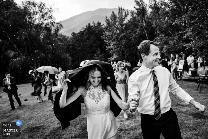The bride and groom recess from the ceremony as it starts to rain at The Hungry Trout Resort in Wilmington | New York wedding photography