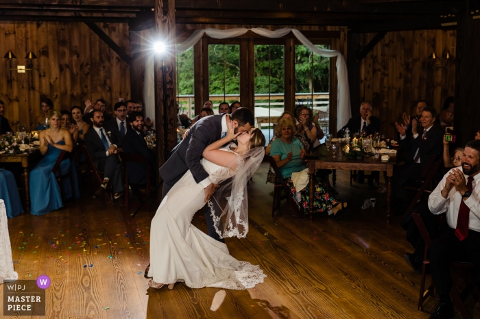 The groom dips the bride and seals it with a kiss as the family and friends cheer them on at The Preserve at Chocorua in Tamworth, NH