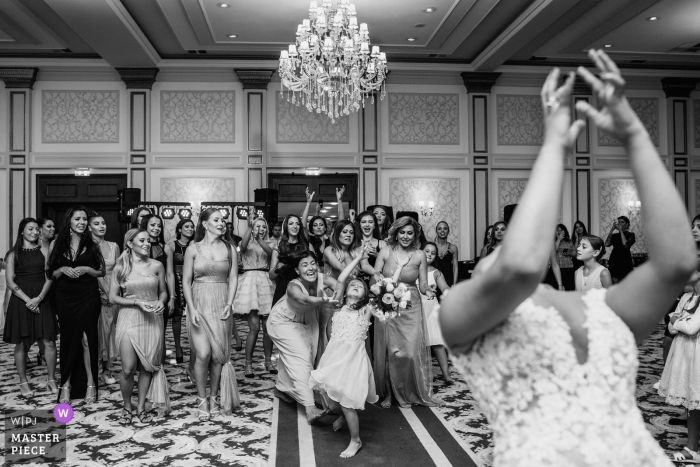 Ramada hotel Sofia wedding reception photography - The young generation try to catch the bride's bouquet of flowers