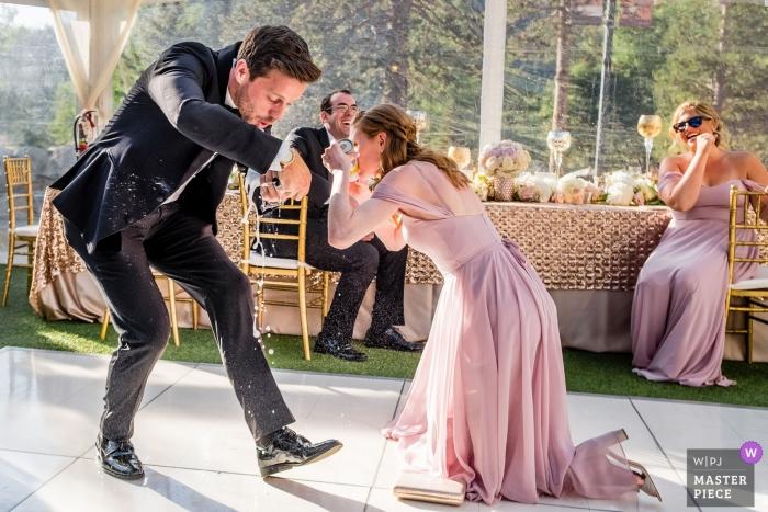 Groomsman and bridesmaid do a grand entrance chug - wedding photography from Resort at Squaw Creek