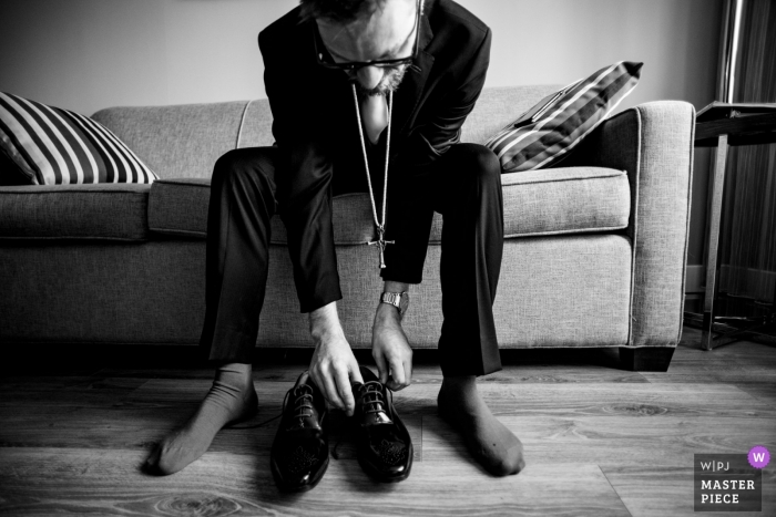 Montreal Wedding Photographer | Groom putting on his wedding shoes, wearing his deceased father's cross in his honour