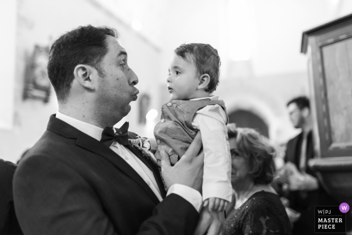 Cuzion wedding photograph of a man making faces at a little child at church