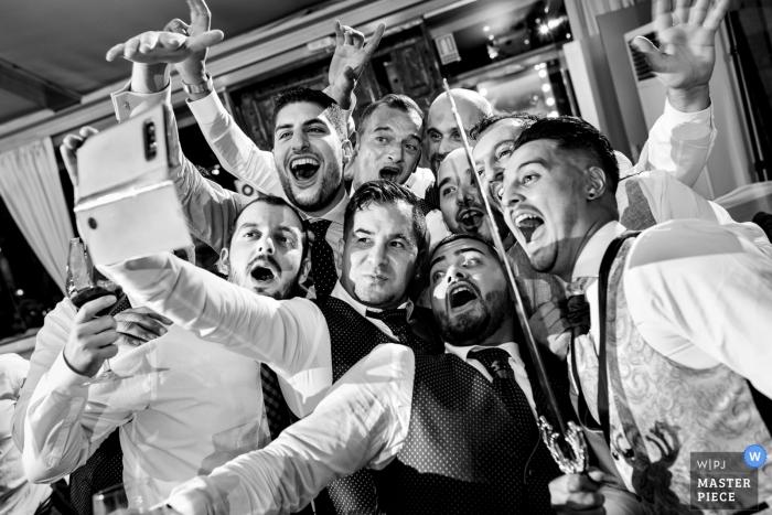 Mirador de Cuatro Vientos wedding photo of the groom and groomsmen taking a selfie (with a sword)