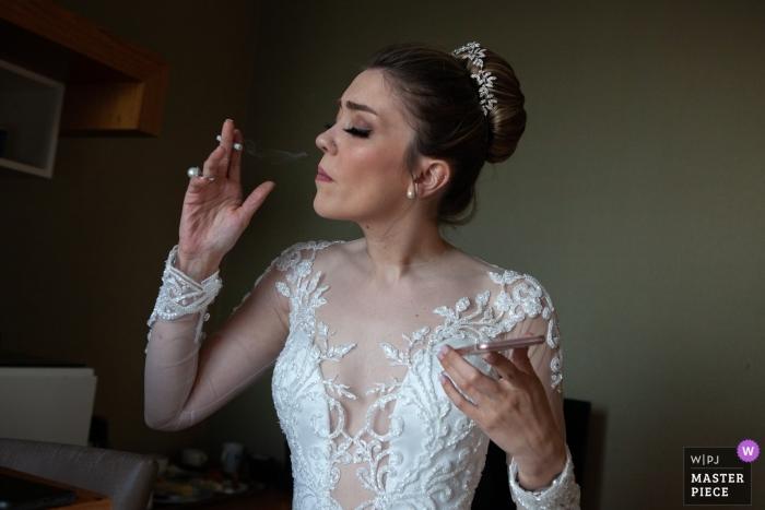 Istanbul, Türkei Hochzeitsfotograf | Braut, die eine Zigarette raucht, um sich mit Telefon in ihrer Hand zu entspannen
