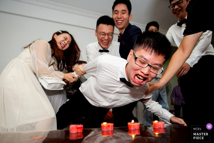 Fujian Groomsman Game trying to blow out candles - China Actual Day Wedding Photographer