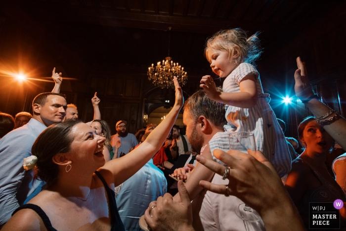 Photographe de lieu de mariage au Château de Maulmont, France - Fête avec une petite fille sur les épaules pendant la réception