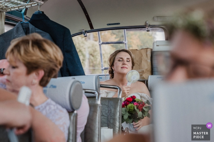 Schloss Nordkirchen summer wedding photography | The bride is too hot - using small fan in back of bus